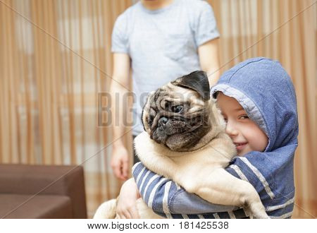 Little boy with pug dog at home