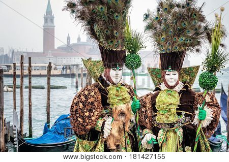 Green and gold masked couple wearing carnaval costumes with peacock feathers, Venice, Italy.