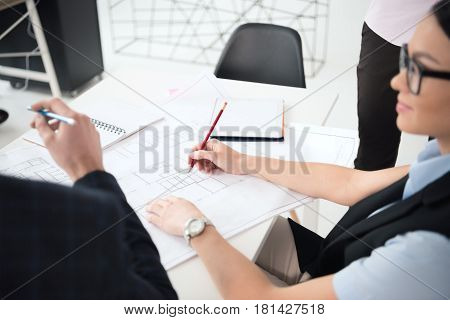 Partial view of young businesspeople holding pencils while sitting at table with blueprint