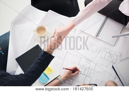 Close-up partial view of businesspeople shaking hands above table with blueprints