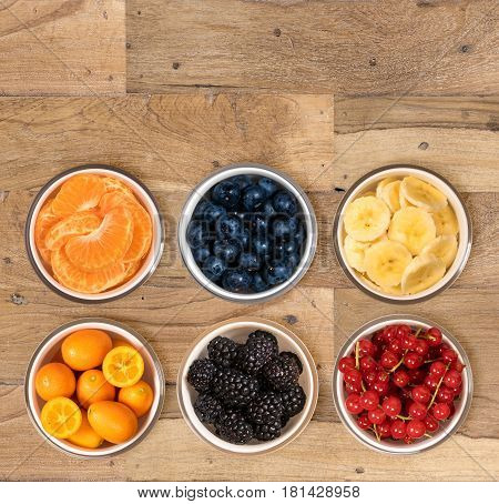 Top view of a white glass bowls of various sorts of organic fruits including, banana, orange, blueberry, redcurrant, blackberry and kiwi berry and sitting on old wood table surface