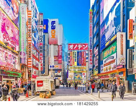 TOKYO, JAPAN - JANUARY 11, 2017: Crowds pass below colorful signs in Akihabara. The historic district electronics has evolved into the shopping area for video games, anime, manga, and computer goods.