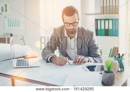 Stylish Handsome Concentrated Man  In Formal Wear Has Ideas And Working With Blueprint Papers And Dr