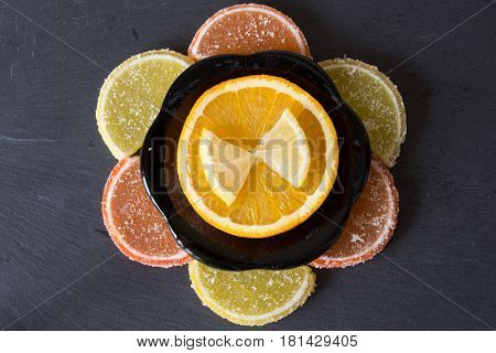 Colorful sugary marmalade like lemon and orange slices covered with sugar. Fruit jelly candies. Dolce vita. Closeup. Top view on slate.
