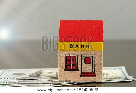 Toy brick bank building sitting on US 100 dollar bills as illustration of too big to fail banks. Repeal of Dodd-Frank could jeopardize the assets of large investment banks