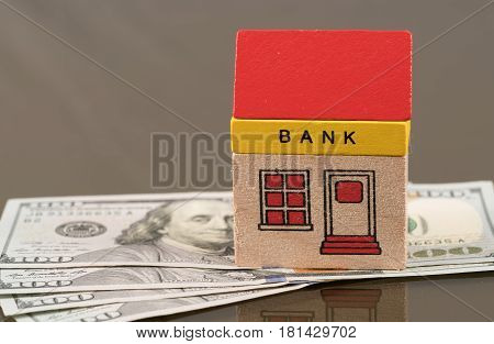 Toy brick bank building sitting on US 100 dollar bills as illustration of too big to fail banks. Repeal of Dodd-Frank could jeopardize the assets of large investment banks poster