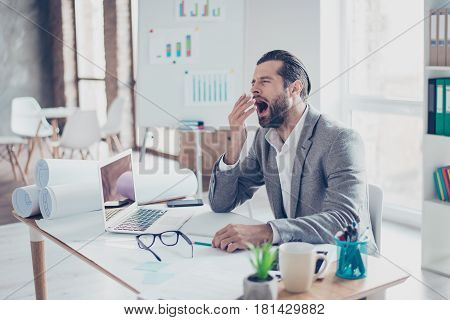 Young Overworked Businessman Yawning In Modern Lightful Office. He Want To Sleep