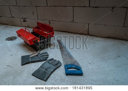 Red metal tool box with many tools on concrete floor
