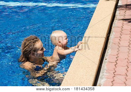 Family on vacation. Mother and baby are swimming in the pool.