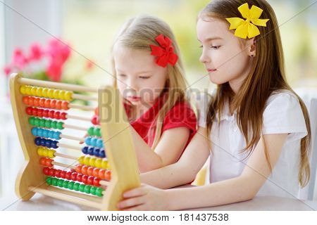 Two Cute Little Girls Playing With Abacus At Home. Big Sister Teaching Her Sibling To Count.