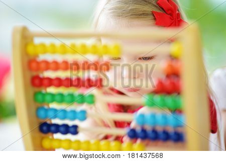 Cute Little Girl Playing With Abacus At Home. Smart Child Learning To Count.