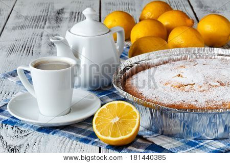 Lemon tart on wooden table with coffee