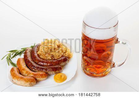 Octoberfest menu beer mug with foam a plate of sausages and sauerkraut. Oktoberfest meal.