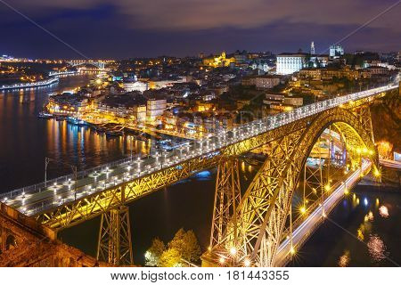 Picturesque aerial view of Old town of Porto, Ribeira and Dom Luis I or Luiz I iron bridge across Douro River at night, Portugal
