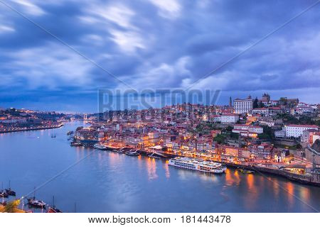 Picturesque panoramic aerial view of Old town of Porto, Ribeira and bridge with mirror reflections in the Douro River during evening blue hour, Portugal