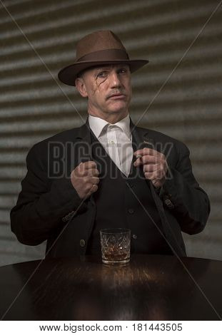 1940s mature male gangster having a drink