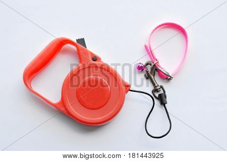 red automatic leash and pink nylon cat collar on white background