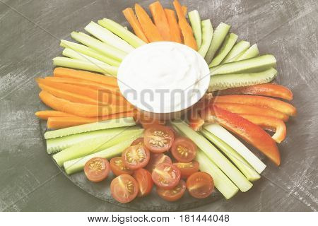 Creamy Sauce In White Bowl And Various Vegetables (tomatoes, A Celery, Cucumbers, Carrots) On A Dark