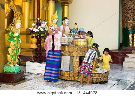 YANGON, MYANMAR-MARCH 2, 2017:  Buddhist family does prayer ritual at Shwedagon Paya pagoda on March 2, 2017 in Yangon. Myanmar. (Burama)
