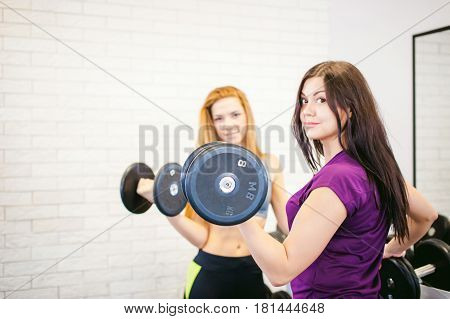 Girl In A Bright White Gym. Two Young Athletic Women Near Sports Equipment Are Preparing For The Tra