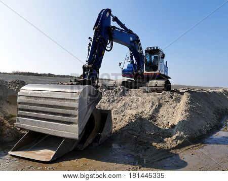 Blue excavator on pile of sand in muddy sand