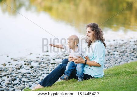 Mother and son hugging and playing near the lake