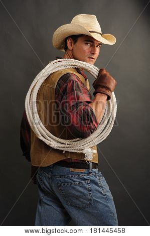The tough looking cowboy is holding a rope.