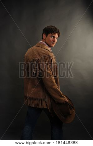 The handsome cowboy is looking back in mystery.
