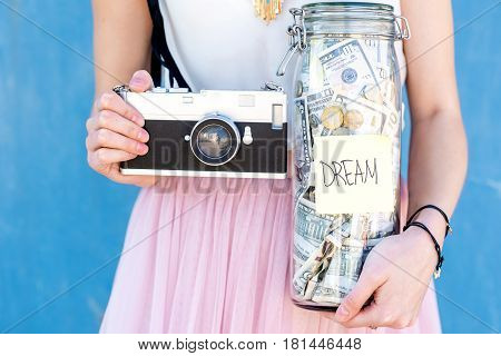Holding a bottle with money savings for the dream standing with photo camera on the blue background. Dreaming to be a photographer