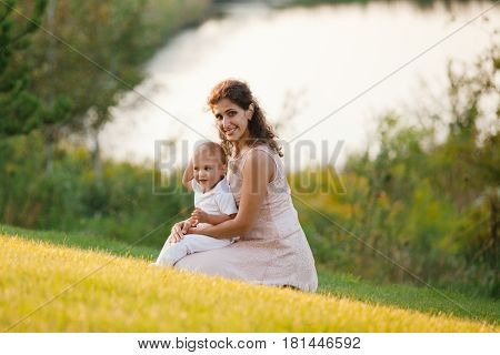 Mother and son playing near the lake