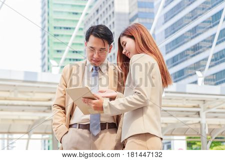 We already have great results! Young beautiful woman pointing at tablet with smile and discussing something with her boss while standing.Success concept