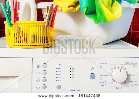 Close up top of modern washing machine in bathroom with facilities on it: cleanser, washing basin with colorful cloth in it, colorful plastic containers and pegs