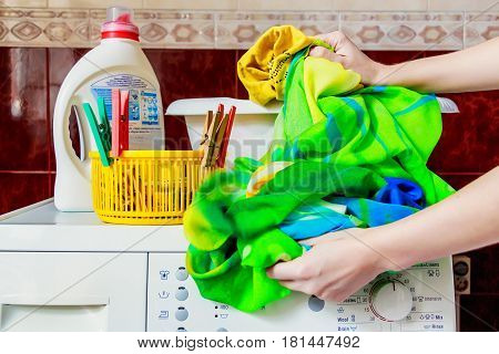 Close up top of modern washing machine in bathroom with facilities on it and female hands putting colorful cloth in wash basin