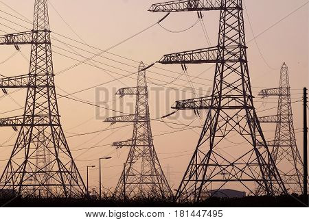 electric pylons and power lines seen in silhouette