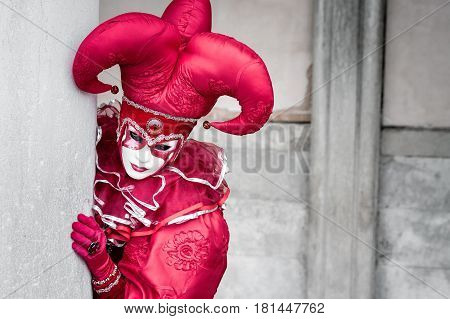 Red mask clown costume peeking behind column at Venice Carnaval, Italy.