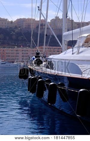 a blue hulled yacht in Monaco marina with water reflections