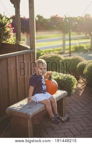 Happy cute little boy spending time outside surrounded by pumpkin