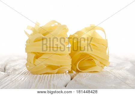 Pasta tagliatelle on a white wooden table