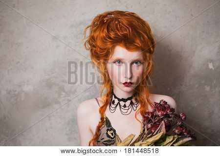 Attractive woman with red hair in a nightgown. Red-haired attractive girl with pale skin and blue eyes with bright unusual appearance with choker around her neck with a bouquet of dried roses. French attractive courtesan. Copyspace. Attractive model