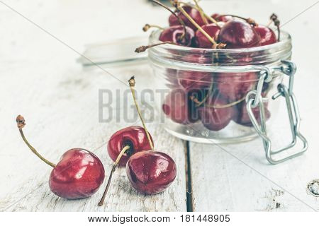 Red ripe juicy cherry in glass jar on white rustic wooden background. Sweet summer berries. Freshly harvested merry. Selective focus.