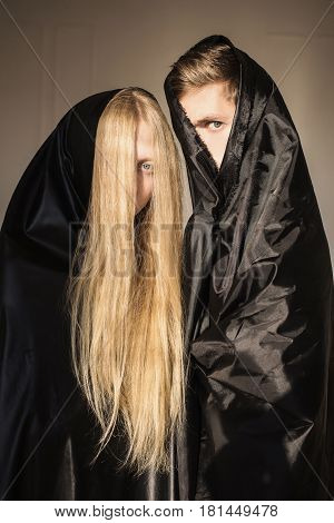 The mystery girl with long blonde hair and a man in black cloth on faces. Conceptual mystery photography. Piercing look. Anonymity. Mystery portrait photography.