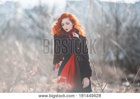 A woman with red curly hair in a black coat at the autumn background. Red-haired girl with pale skin and blue eyes and a bright unusual appearance with a scarf around her neck. Street style