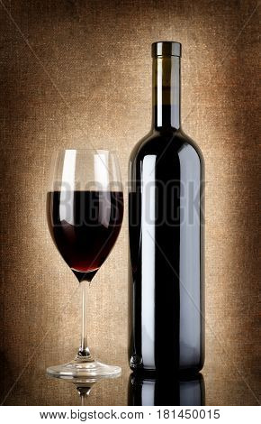 Wine bottle and wineglass on a background of old canvas