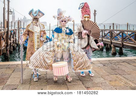 Blue and gold masked elegant trio with carnaval costume, Venice, Italy.