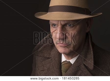 Mature man dressed as a 1940s gangster, on a grey background, taken with copy space