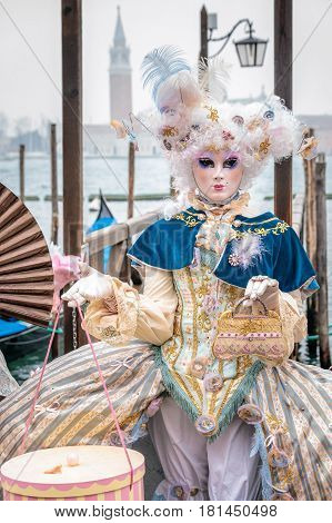 Blue and gold masked minx girl wearing carnaval costume with elegant handbag and cake box, Venice, Italy.