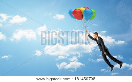 A businessman holding a batch of colorful balloons that let him fly through the clouds. Business and dreams. Dreaming big. Motivation and results.