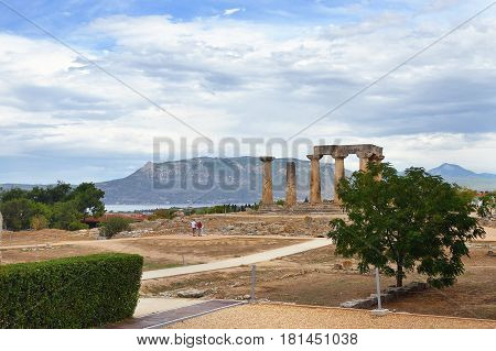 Ancient Corinth and view on the Temple of Apollo under dramatic cloudy sky at sunset in Greece