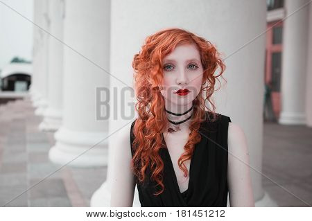 Woman with long curly red hair in a black dress against the background of the column. Red-haired girl with red lips pale skin blue eyes a bright unusual appearance in the city