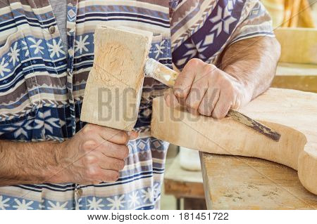hands of carpenter processing wood with a chisel